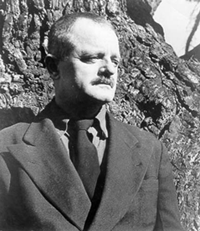 Kenneth Rexroth in suit at tree