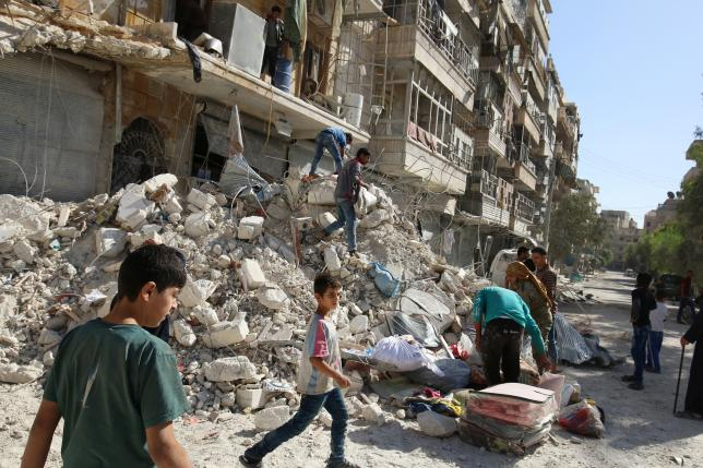 People remove belongings from a damaged site after an air strike Sunday in the rebel-held besieged al-Qaterji neighbourhood of Aleppo, Syria. REUTERS/Abdalrhman Ismail